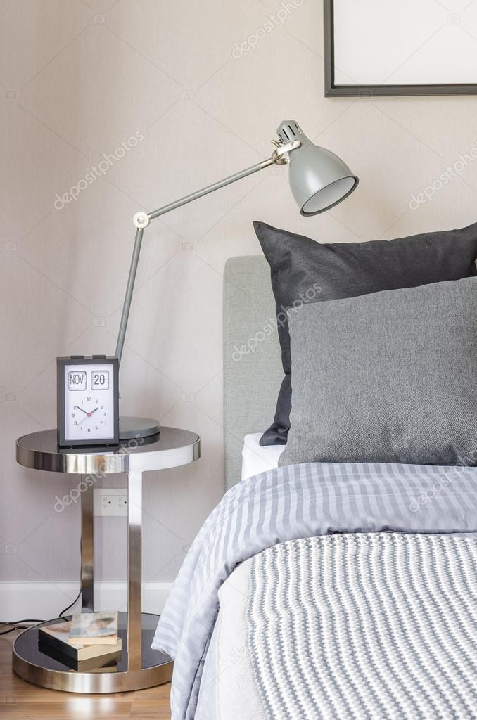 Moderne graue Lampe mit Wecker auf Beistelltisch im ...
