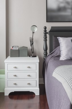 Wooden white table bedside with black lamp