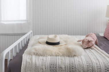 Pink doll on white wooden bed and classic hat