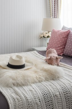Pink pillows with pink doll on white wooden bed and classic hat