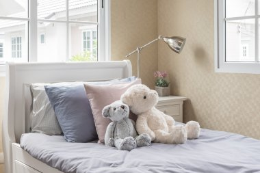 Kid's bedroom with dolls on white wooden bed