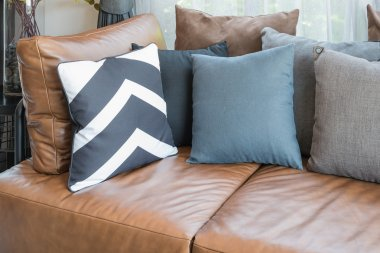 pillows on brown leather sofa i