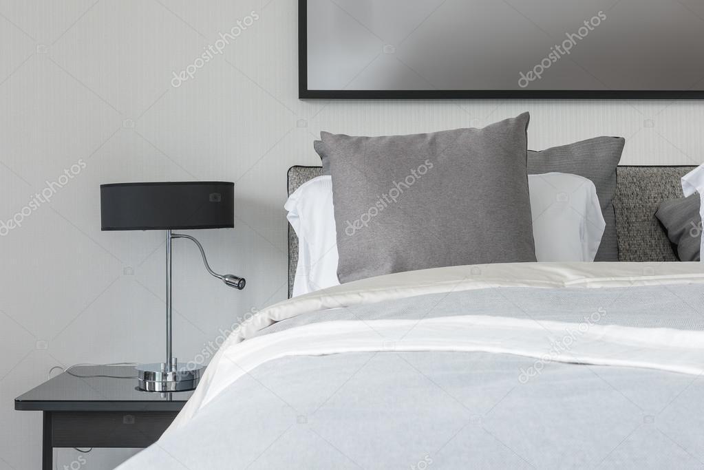 Graue kissen weiß bett im modernen schlafzimmer mit schwarz lampe