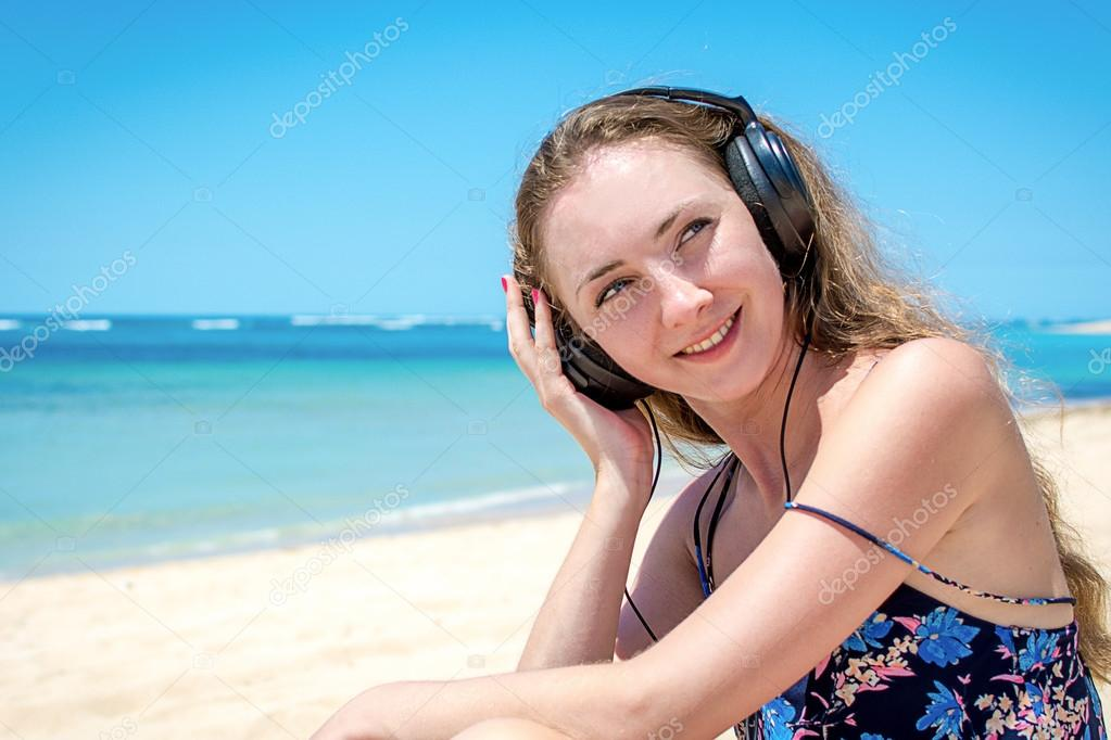 Young girl relaxing and listening to the music at the beach