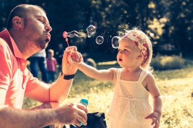 daddy and daughter blowing bubbles