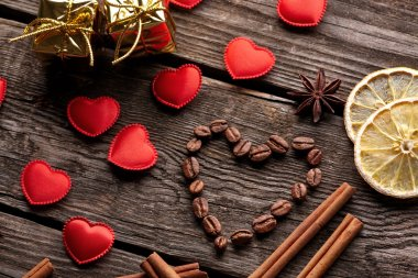 Coffee beans in shape of heart with cinnamon small red hearts and lemon on old vintage wooden background. Close-up. stock vector
