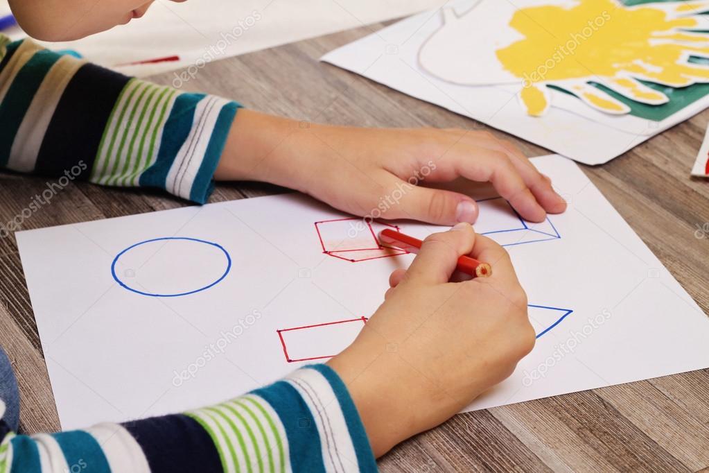 Escuela niño dibujando figuras geométricas en papel con lápiz ...