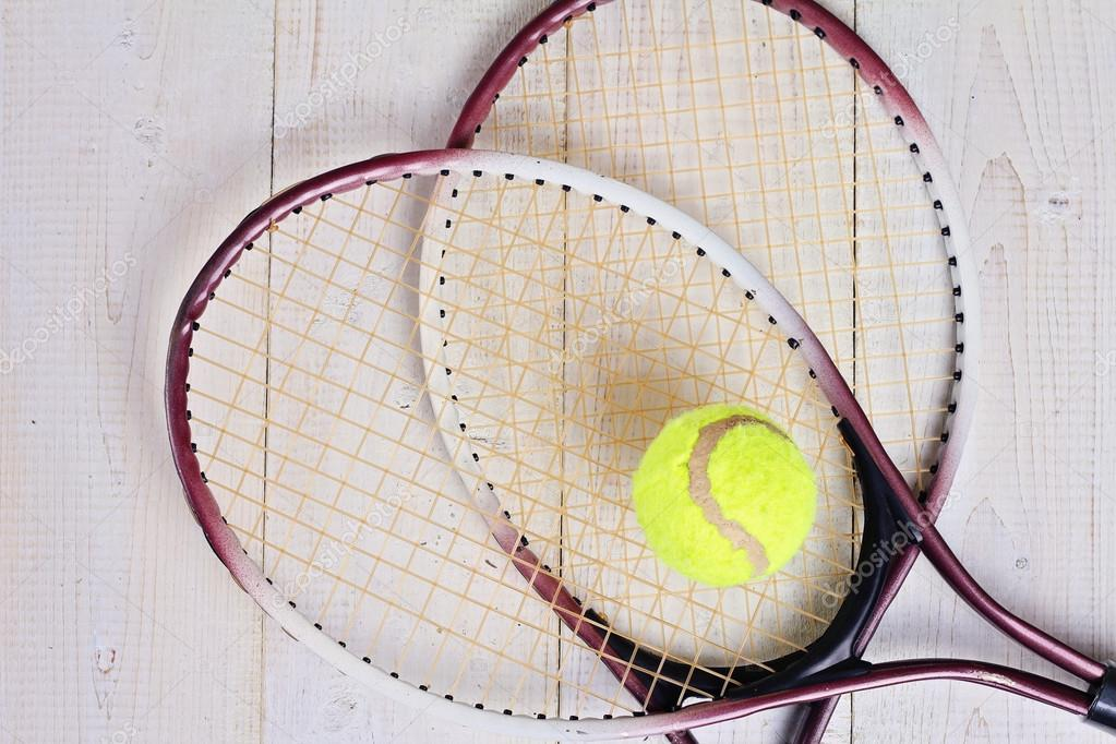 Heart shape made from tennis rackets. Close up on tennis racket and ball. Sport equipment background, wallpaper.