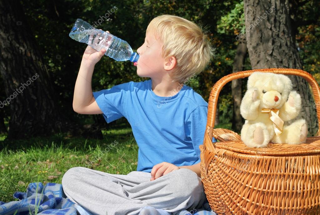 Outdoor portrait of 5 year old boy drinking water from bottle in park.   Picnic, Family,holiday, weekend concept