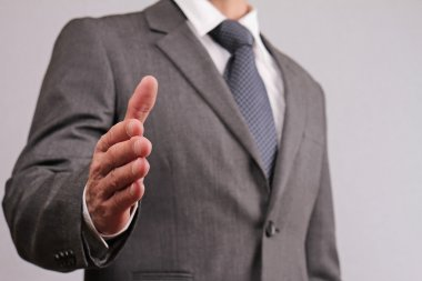 Close up of businessman with open hand ready to seal a deal gesturing a hand shake. Meeting new business partners, partnership, negotiations, presentation