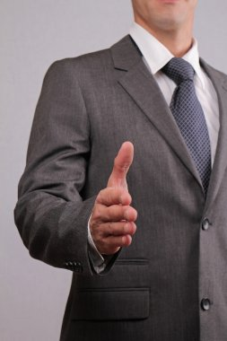 Close up of successfull businessman with open hand gesturing a hand shake. Meeting new business partners, partnership, negotiations, presentation
