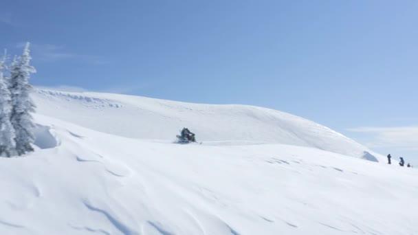 Snowboarder fahren am Wintertag mit Motorschlitten auf winterlichen Berggipfeln