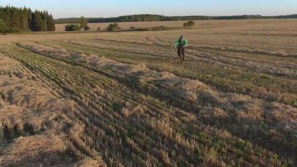 Mann mit grünem Helm Kapuzenpulli und roter Sonnenbrille fährt schnelles Mountainbike-E-Bike quer über das Feld zur Drohne. Schneiden von Gras und Holz am sonnigen Sonnenuntergang Herbst Abend Luftaufnahme rückwärts