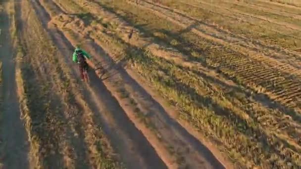 Mann mit grünem Helm extrem schnelle Fahrten auf orangefarbenem MTB-Fahrrad Elektro-Mountainbike Vollfederung E-Bike ländliche schmutzige Straße Staub von den Rädern vorbei am Feld an sonnigen Herbstabend Luftaufnahme