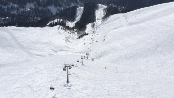Luftaufnahme von oben Seilbahn alpines Skigebiet mit atemberaubender natürlicher Berglandschaft. Aufnahmen aus der Hubschrauberseilbahn in hügeligem Gelände, umgeben von Schnee Wintersaison