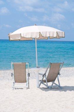 two deckchairs on the beach under an umbrella