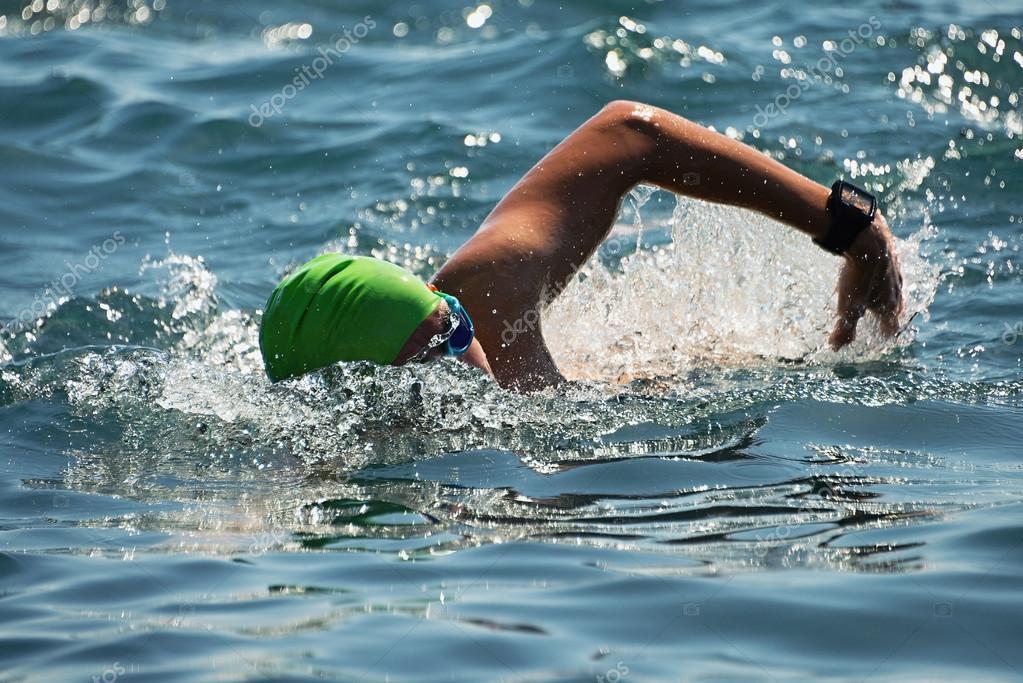 青い海でクロールを泳ぐ男性スイ...