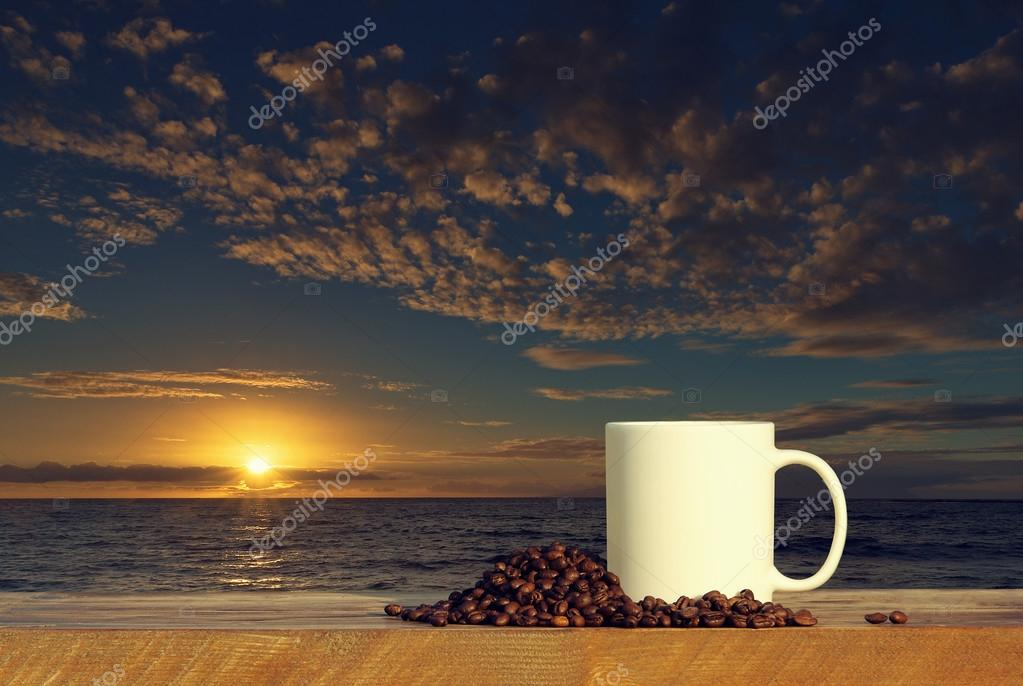 Coffee cup on wood table at sunset or sunrise ocean