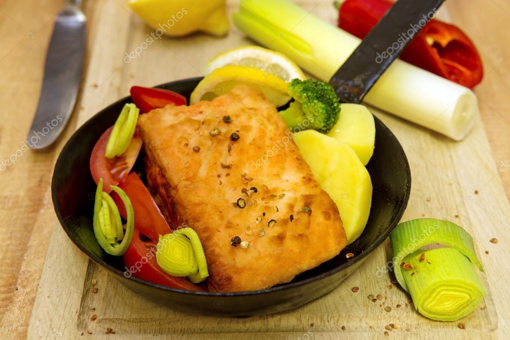 Salmon steak fried in frying pan.