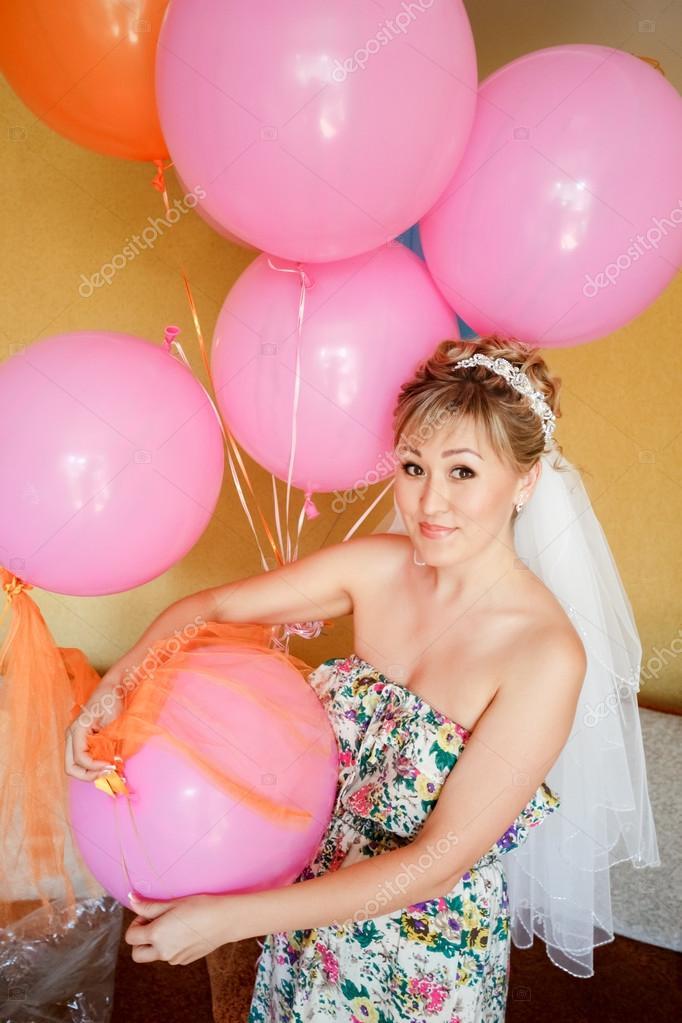 Novia en ropa casual con velo entre globos de color rosa ...