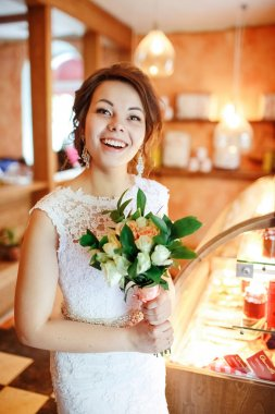 Emotional beautiful bride with wedding bouquet in interior, joyful surprised face, facial expression.