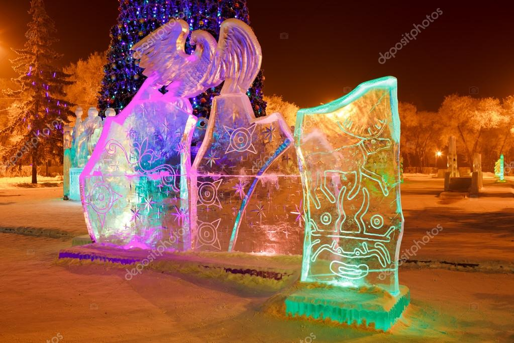 Ice sculpture in the city park on Christmas and New Year with cave paintings of deer, mythical creatures, solar signs, petroglyphs. Illuminated at night.