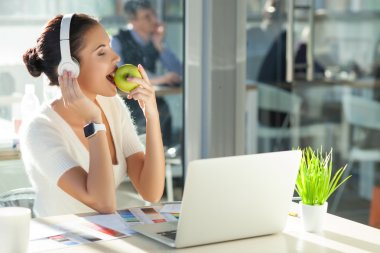 Cute young businesswoman is resting in office