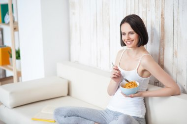Happy young woman having breakfast
