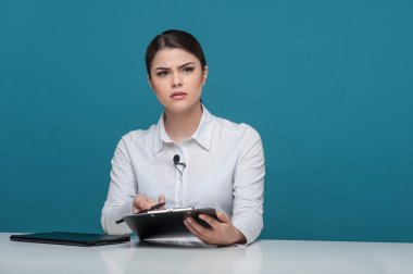 Beautiful girl tv newscaster reports holding notebook