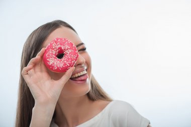 Cheerful young woman is playing with sweet food