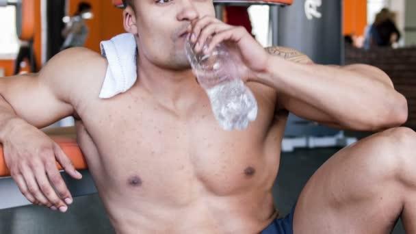 pohledný mladý sportovec odpočívá ve fitness centru
