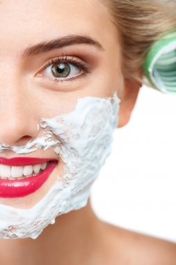 Cheerful young woman with pretty smile is shaving