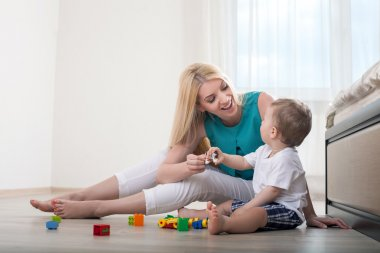 Cheerful young mother is playing with her son