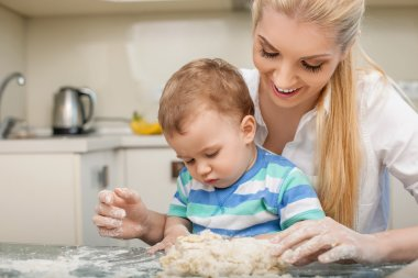 Cheerful young mom and her small son are baking