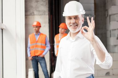 Successful senior architect is showing okay sign. He is pleased with building. The man is smiling. Handsome young workers are standing and resting behind him stock vector