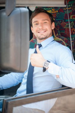 Cheerful young male driver is expressing positive emotions