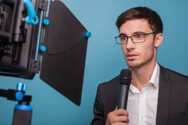 Attractive reporter is holding a microphone and telling news. The man is looking at the camera seriously. He is wearing suit and eyeglasses. Isolated on blue background stock vector