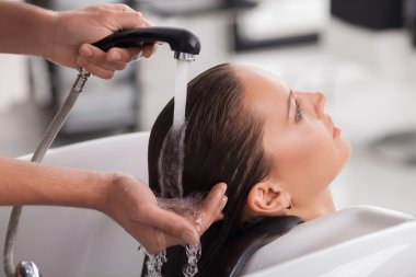 Pretty young woman has her hair washed by hairdresser