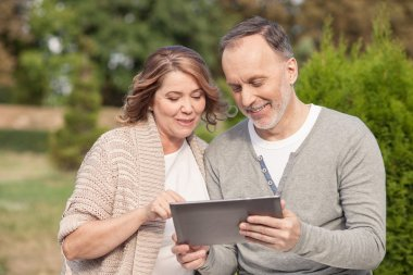 Pretty old husband and wife are using a tablet