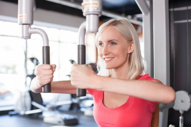 Attractive young woman is training in fitness center