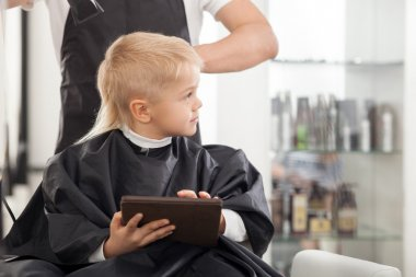 Professional young barber is making hairstyle for kid