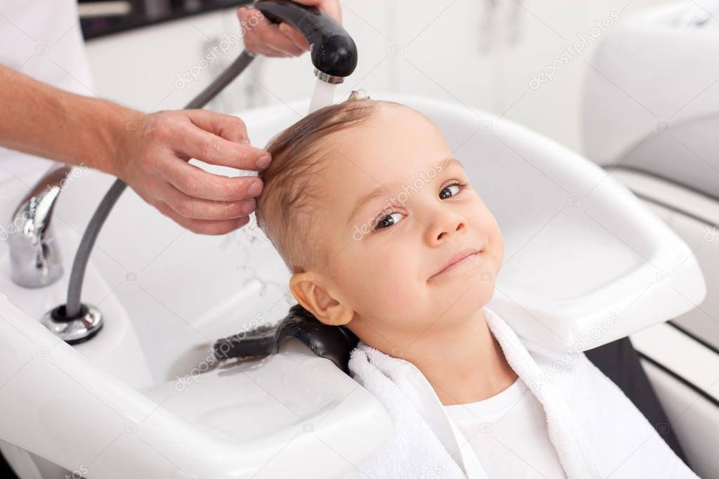 cheerful male child is having hair washed in salon ストック写真