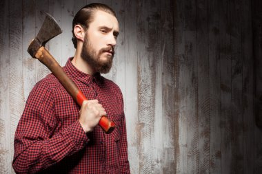 Handsome young guy with beard and hatchet