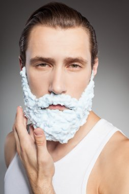 Attractive young bearded man shaves with joy