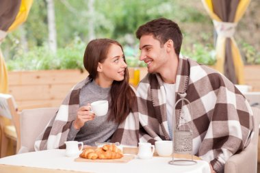 Cheerful young loving couple is dating in cafe