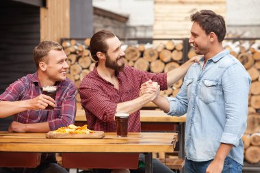 Attractive young guys are greeting in beerhouse