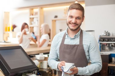 Handsome young male barista is washing crockery in cafe