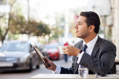 Handsome man with suit is using laptop in cafe