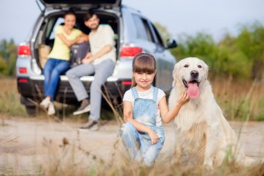Cheerful parents and child with puppy near vehicle