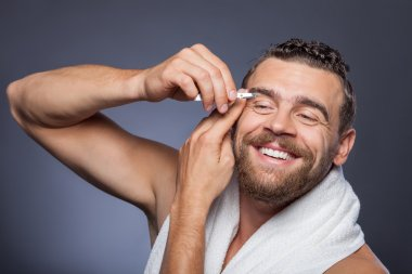 Attractive bearded guy is caring of his appearance